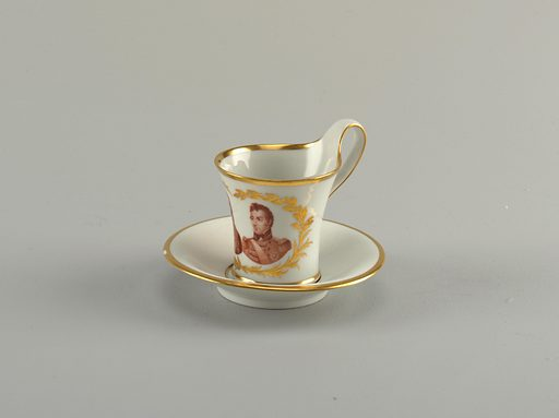 Battle of Waterloo commemorative cup with concave sides, with greatest diameter at lip. Flat strap handle. Flat saucer, horizontal ogee marly. Cup has bust portraits of Arthur Wellesley, 1st Duke of Wellington and Gebhard Leberecht von Blücher, encircled by gold palm and laurel branches. Saucer has gold inscription: Sieger / bei La belle Alliance / 1815 (Winners, the Beautiful Alliance). Date: 1810s. Record ID: chndm_1938-57-494-a_b.