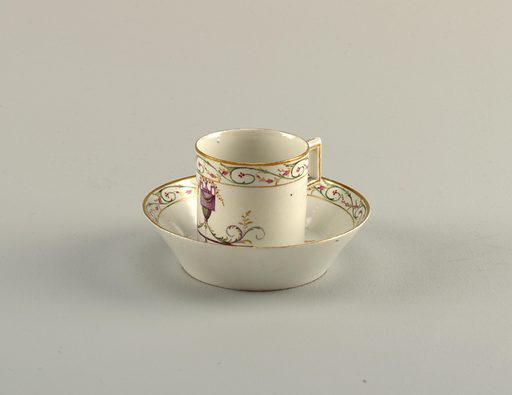 Cylindrical cup, rectangular strap handle. Flat saucer with flaring sides. Decoration in pale colors, of an urn with foliate rinceaux, and bands of foliage in colors and gilding. Date: 1800s. Record ID: chndm_1938-57-677-a_b.