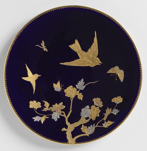 Round plate with blue glaze ground. Pressed gold paste decoration of birds and flowering branches. Scalloped gilt border. Date: 1880s. Record ID: chndm_1993-134-20.