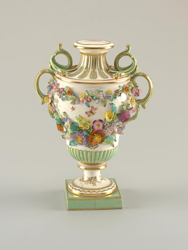 On a square pedestal, a footed pyriform urn, reeding on its lower portion and fluted on contracting neck. Body covered with garlands of applied flowers. Triple-scrolled handles, green and gold. Flowers are polychrome on a white body. Date: 1820s. Record ID: chndm_1962-155-1-b.