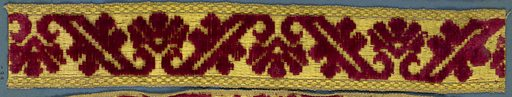Trimming fragment in a design of flowers separated by leaves ending in scrolls. In red cut velvet on a yellow ground. Made in: France. Date: 1800s. Record ID: chndm_1909-2-33.
