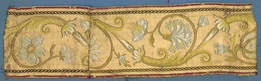 Blue, white, yellow, green and gold trimming fragment in an incomplete design showing flowers, leaves and scrolls. Made in: France. Date: 1800s. Record ID: chndm_1909-2-49.