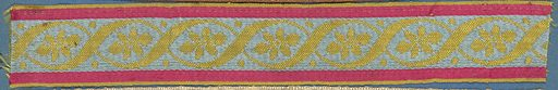 Trimming fragment in a design of crossing ribbons enclosing six-petal flowers; in yellow on blue ground with red borders. Made in: France. Date: 1800s. Record ID: chndm_1909-2-89.