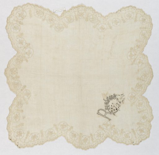 """Handkerchief in piña cloth with scalloped edge, buttonholed and with border of flowering vine, embroidered in cotton, crossing circles of drawnwork. Corner in black and white with word: """"Recuerdo"""" with bird above and small dog or cat below flowers. Made in: Philippines. Date: 1800s. Record ID: chndm_1951-111-77."""