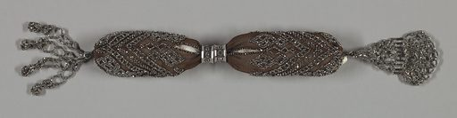 Dark crocheted silk ornamented with cut steel beads in diagonal bar patterns and diamond shaped areas. Two hexagonal steel rings control side opening; ornamental pendant of steel beads and bars at one end; steel beads form tassel at the other end. Made in: France. Date: 1800s. Record ID: chndm_1953-106-25.