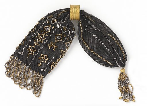 Crocheted black silk ornamented on one end with single lengthwise bars of alternating rows of gold and cut steel beads; the other end is decorated with gold and steel beads in a six-pointed star and diamond pattern. One gold ring controls side closing. One end is fringed, the other tasseled, both with cut steel and gold beads. Made in: France. Date: 1800s. Record ID: chndm_1953-106-41.