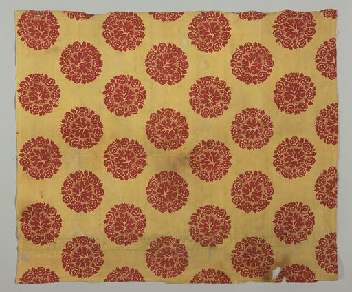 """Mustard yellow ground, printed in detached circular design of flower wreath framing leaf, in bright red. Design arranged in staggered rows, each element about 3 3/4"""" across. Printing appears to be by block, superimposed on the yellow ground. Picotage around leaf. Both selvages present. Pieces of yellow 2/2 twill fabric used on the pieced side as part of the border. Made in: Europe. Date: 1800s. Record ID: chndm_1954-6-1."""