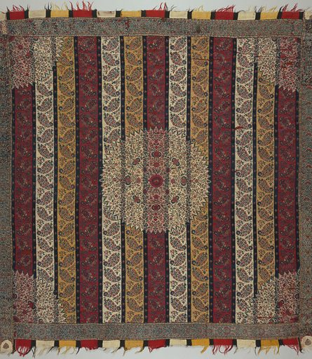 """Square """"moon shawl"""" with guard borders on four sides and fringed borders at warp ends only. Broad vertical stripes of red, yellow and white with floral cones, separated by narrow stripes of dark blue. Circular central medallion, with a quarter-circle medallions in each corner with stylized floral filling in blues and red on pink and white ground. Coarse woven border with stylized floral motifs on four sides. Separate borders top and bottom imitate fringed warp ends. Made in: India. Date: 1800s. Record ID: chndm_1955-133-16."""