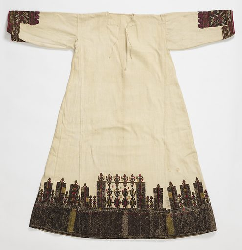 Long dress of heavy white cotton, straight sleeve, body flares slightly at hem as long, wedge-shaped pieces are sewn in from under arm to hem. Ornamented at the hem with a deep border of embroidery in black, brown, olive green and red. Design is highly stylized: at bottom, solidly worked from 6 3/4 inches in narrow bands of zigzag patterns; above, an arrangement of pillar-like forms and stylized plants, with a plant at the top of each pillar, so that the whole suggests a wall. Height of the whole border is 14 inches. Cuffs of sleeves are also finished with a deep border of embroidery in brown, red, white and yellow silks, in geometric forms. Mainly cross stitch; on sleeve coarse darning stitch. Made in: Greece. Date: 1800s. Record ID: chndm_1955-133-30.