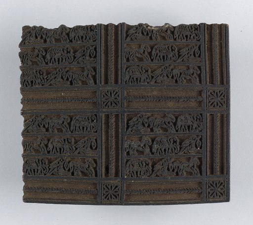 Carved block design shows squares containing very small animals arranged in rows. These squares are separated by strips with little medallions at crossings. Design is in relief. Block would print one corner of the pattern. Made in: India. Date: 1800s. Record ID: chndm_1957-123-3.