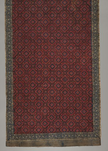 "Red and blue batik sarong. Shows ""ceplokkan"" pattern: flowers or blossoms, symmetrically distributed over surface, stylized, star-like,and contained within a geometric shape. Borders show batiked on fringe. Made in: Palembang, South Sumatra, Indonesia. Date: 1800s. Record ID: chndm_1961-115-30."