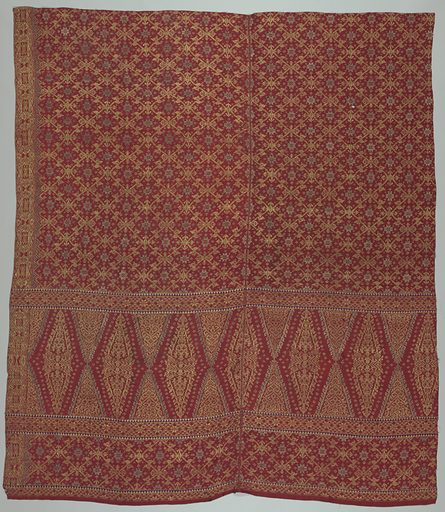 """Red silk brocaded cloth (kain songket) with all-over geometric pattern of stars and rosettes in gold brocade, with wide panel at one end showing the """"tumpal"""" motif (row of isosceles triangles). Geometric border in gold. Made in: Bali, Indonesia. Date: 1800s. Record ID: chndm_1961-115-7."""