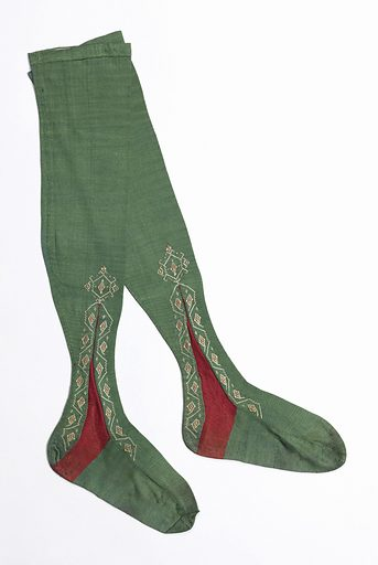 Pair of green knitted silk stockings with a red insertion at the ankle surrounded by embroidered decoration in pink and white. Made in: France. Date: 1800s. Record ID: chndm_1962-55-14-a_b.