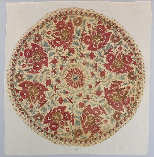 Round fragment of cream-colored cotton block printed in reds, violet, and green. A floral pattern is arranged to fill a circle of flower heads. Center round medallion has a stylized flower head forming a rosette. Made in: India. Date: 1800s. Record ID: chndm_1968-73-2.