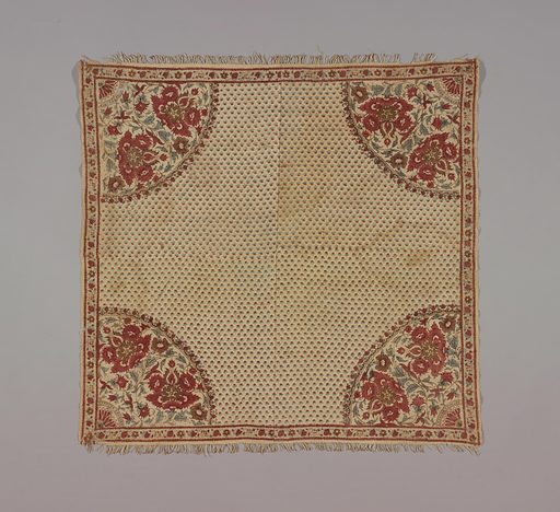 Small square table cover, pieced, of cream-color cotton block-printed in reds, violet, and green. Corner design of large flowers and foliage; small all-over pattern of little buds. Narrow floral border. Green is blue over yellow. Made in: India. Date: 1800s. Record ID: chndm_1968-73-3.