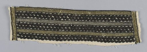 Portion cut from a sleeve of heavy white cotton. Bars of black cotton embroidery in simple repeat pattern are separated by rows of metallic embroidery in chain stitch. Made in: Balkans. Date: 1800s. Record ID: chndm_1969-86-6.