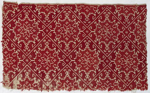 Rectangle of off-white linen embroidered in red silk in an allover pattern of interlocking diamonds containing eight-pointed stars. The background is embroidered in red; the design is reserved in the linen ground. Made in: Naxos, Greece. Date: 1800s. Record ID: chndm_1971-50-137.