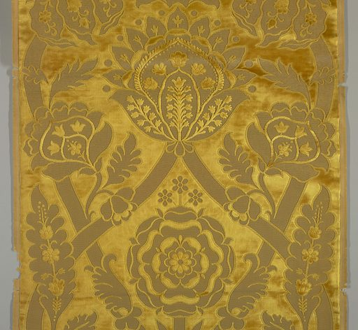 Design of crown, large flower and Tudor Rose and curving straps. Gold color. Woven as a sample with header top and bottom. Made in: probably Europe. Date: 1880s. Record ID: chndm_1979-9-30.