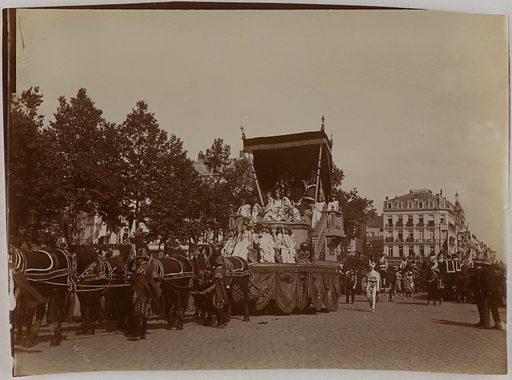 Chevaux tirant un char de carnaval avec deux jeunes femmes tronant entourées de petites filles. Numéro d'object: CARPH060339.