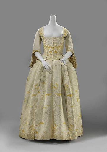 Tablier, pleated all around with wide center pleat of cream-coloured silk embroidered in yellow with slender, broadly measured flower and leaf tendrils; blue linen lining. Origin: ? France. Date: 1740 – 1745. Object ID: BK-1961-90-B.