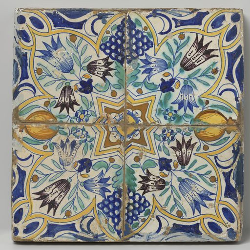 Four tiles that together form a star surrounded by tulips, bunches of grapes and pomegranates. Origin: Netherlands. Date: c 1600 – c 1625. Object ID: BK-1955-256-A.
