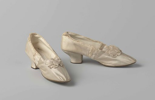 Women's shoe in ivory white satin with a multi-loop bow and glass beads in the center. Origin: England. Date: c 1890. Object ID: BK-1962-24-A.