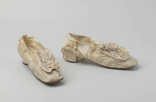 White satin ball shoe with bows on the front shoe, square toe and three-quarter heel. Origin: Netherlands. Date: c 1850 – c 1860. Object ID: BK-NM-13083-B-1.