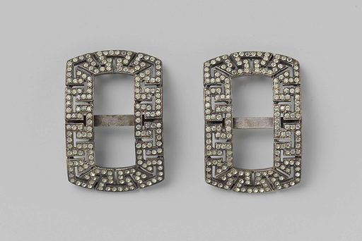 Shoe buckle of silver-plated metal in the shape of a horizontal rectangle, with angular meanders, with rhinestones. Origin: ? France. Date: c 1900 – c 1925. Object ID: BK-1967-63-B.