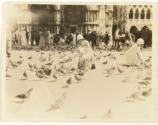 American tourist feeding pigeons in Piazza San Marco, Venice, Italy