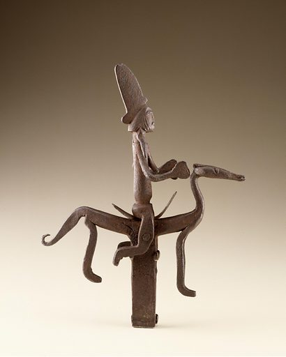 Iron staff finial composed of a female figure with flat, conical hat sits astride a horse on a curved saddle. The shaft of the staff is cut off just below the level of the horse's hooves. Date: 1800s. Record ID: nmafa_85-19-1.