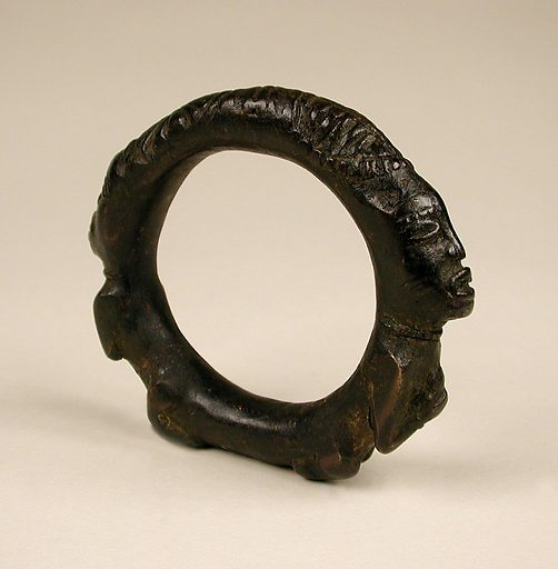 Copper alloy bracelet composed of two figures, facing in opposing directions, on the outer surface. The figures have bent legs, and the arms are bent onto the chests. One figure holds a chewing stick to the mouth with the right hand; the other figure's right hand grasps the left arm. Both faces have raised bands forming open eyes and mouths. Between the two heads are a rosette, raised lines across the surface and a cowrie shell motif. Date: 1600s. Record ID: nmafa_88-7-3.