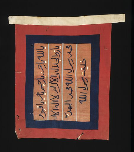 Double sided rectangular cloth flag with a central brown silk panel surrounded by a blue-black cotton border with an outer red cotton border, and a white cotton tube for a pole support. The central panel contains four lines of appliqued Arabic script in blue-black with white diacritical marks and seperated by pale blue lines. One word is appliqued in green. Date: 1880s. Record ID: nmafa_91-20-1.