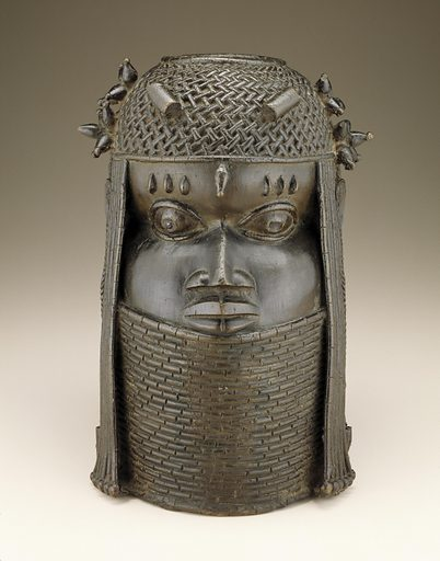Cast copper alloy cylindrical head with a beaded neck to the lower lip of the mouth, netted bead cap with clusters of beads on the sides, cylindrical beads in front, strands of beads in front of theears, braids behind the ears and a single large bead on the forehead. The face has 3 keloids over each eye. Date: 1700s. Record ID: nmafa_85-19-16.