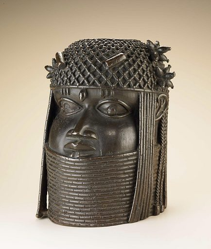Cylindrical cast copper alloy hollow head with iron inlay in the eyes. A representation of a beaded collar covers the neck to the lower lip and a cap of netted beads with projecting clusters and braids. The head has a single cluster of projecting beads on the proper right side, with two on the left, and a circular hole in the top of the head. Date: 1700s. Record ID: nmafa_2005-6-18.