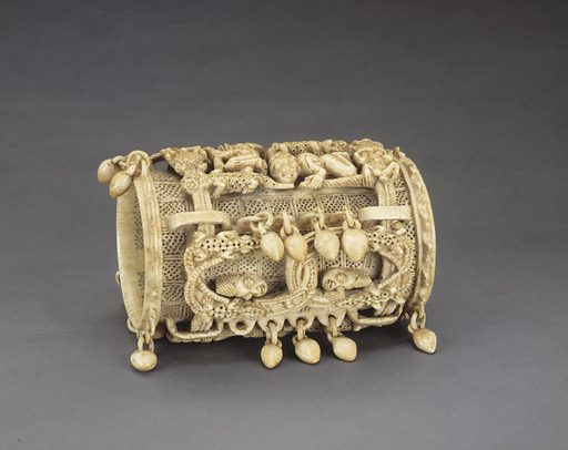 Ivory bracelet with entire surface carved with human-like figures, heads and animals in high relief on a background of fine lattice rectangular panels. Ivory bead-like additions hang from the carved rings to the side and to each end. Date: 1590s. Record ID: nmafa_2005-6-8.
