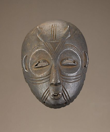 Wood face mask with broken horns projecting from the forehead, circular eyesockets and semicircular slit eyes. Incised linear marks divide the forehead, circle the eyes and flank the mouth. The mask has an overall dark colour. Date: 1840s. Record ID: nmafa_2005-6-189.