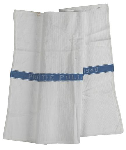 """White cotton with a small basket weave patterned rectangular Pullman Company towel. At the center of the towel is a blue fabric band with a small curved line decorative stitched boarder. Stitched in white thread at the center of the blue band is: """"PROPERTY OF THE PULLMAN COMPANY 1940"""". Date: 1940s. Record ID: nmaahc_2012.46.75.3."""