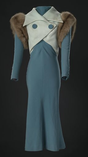 """Light green wool twill cropped vest with fur-trimmed armholes worn by Diana Ross as Billie Holiday in the Paramount Pictures produced 1972 film """"Lady Sings the Blues."""" The vest has an open shawl collar with pointed lapels. The proper right front crosses over the proper left front and snaps closed with green fabric covered snaps. There are four snaps, three along the proper right bottom edge and one at the point of the proper left side, and one hook along the bottom right edge that attaches to a thread loop on the left side. Two large teal covered fabric round buttons sewn on the proper right front are decorative. The vest ends at a point at the center back, and a weight is sewn between the facing and lining at this center back point. Brown fur is sewn around the arm openings. The vest is fully lined in light green silk satin. There is a panel of teal lining fabric at the arm openings and the fur trim is lined with black satin. All of the lining is hand sewn. Date: 1970s. Record ID: nmaahc_2012.64.4.2."""