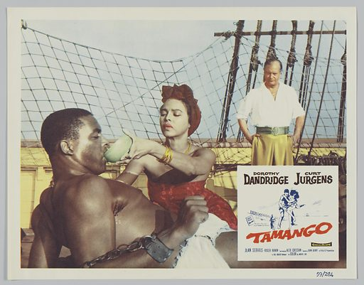 """This lobby card for Tamango depicts three people, two men and one woman on the deck of a ship. The first man is shirtless and shackled by his wrists to the deck. The woman is pouring something in his mouth from a bowl. The woman is wearing gold jewelry and a red head wrap matching her red dress. The third man is standing behind the woman dressed in a white shirt and light-coloured slacks as he looks at the first man and woman depicted. A smaller inset white square in the lower right corner has a line drawing of a woman struggling in a man's arms. Black, red and blue text reads """"Dorothy/ Dandridge Curt/ Jürgen's/ The story they said/ could never be filmed! / Tamango."""". Date: 1950s. Record ID: nmaahc_2013.118.142.7."""
