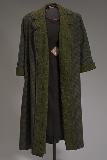 """Green coat worn by Oprah Winfrey as the character Sofia Johnson in the film """"The Colour Purple."""" The full-length, long-sleeved, single-breasted coat is made from a dark green wool tweed plaid. The coat closes at the front with five (5) large round olive fabric-covered buttons that fasten using loops of black cord sewn to the edge of the proper right front. The front sides are turned open and stitched down near the and along the outer edges, making the button and loop closure non-functioning. A wide band of olive wool with stumpwork embroidery in olive rayon of a highly stylized leafy vine design is sewn around the front sides and around the collar, and is cut to follow the tapering of the turned front and the rounded notches at the turned collar. This same olive embroidered band is sewn around the cuff of both sleeves, which are also turned. The sleeves are slightly gathered using a length of the wool plaid attached at the exterior of each sleeve just above the cuff with two (2) round olive fabric-covered buttons, with the strips lined in green rayon. There are two (2) inset pockets, one on each exterior hip of the coat, with notched flaps made of the green plaid and light brown wool lining. Date: 1980s. Record ID: nmaahc_2014.184.1.2."""