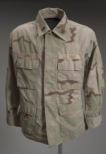 Light coloured camouflage United States Army jacket. Jacket has four (4) pockets on the front, two (2) on each side of the torso, one above the other. Above the upper pocket of the PR side is the name of the wearer [JONES]. On the PR shoulder are two (2) patches, the upper most being a unit patch. The unit patch is a 3rd Personnel Command ACI patch that features three (3) rings interlocking around a sword. The sword's tip points upward. The second patch on the PR shoulder is the American flag outlined in yellow. The flag's stars face toward the front of the jacket. On the PL side of the front of the jacket above the upper pocket is additional stitched text [US ARMY]. On the PL shoulder is another unit patch with flames radiating out of a tiered structure. The unit patch is for the District of Columbia Army National Guard. Down the front of the jacket are five (5) plastic beige buttons. Both cuffs have two (2) buttons each. On the collar are two (2) patches, one on either side of the front of the collar. On the PL front of the collar is a black bar patch indicating the wearer is a first lieutenant. On the PR side of the collar is a patch with the Army Signal Corps insignia. At the nape of the neck of the collar is the clothing tag with care instructions, size and manufacturer information listed. Adhered to the tag is a small line of green tape with stamped text [JB433]. Date: 2000s. Record ID: nmaahc_2014.245.2.1.