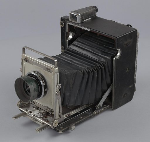 This Pacemaker 34 Crown Graphic camera is an open and extended field camera. It is missing a handle on its PL side, although the holes and indentations demonstrating where the handle was once attached are still present. There is a lens hood with chipping green lacquer attached to the front of the camera which shields a 135mm f/4.7 lens. The metal frame is rusting in multiple spots and the leather finish on the casing is scratched or fading in some places. The folded, leather-like material of the camera's middle body has small punctures at some of its edges but appears to be mostly whole and without cracking in the material. All hinges and screws necessary to collapse and unfold the camera appear to be in full functioning order with no visible signs of loss or severe rusting. There is engraved text encircling the lens which reads [TRADE Rapax MARK / WOLLENSKA 135MM f/4.7 W RAPTAR No 566116]. Date: 1940s. Record ID: nmaahc_2014.302.2.