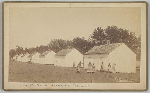 """A cabinet card with an albumen print of five (5) women and three (3) men standing next to a row of white-washed wooden buildings identified in the title as """"Negro Cabins on Kenilworth Plantation."""" The cabins are arranged in a line, with the photographer positioned so that they recede into the distance from right to left in the frame. Treetops are visible behind the buildings. The people are mostly gathered in front of the foremost cabin, though two men stand between this cabin and the one next to it. The photographer's name is imprinted in the image in the lower right. The title is handwritten in black ink on the bottom of the mount. A gilt frame is printed onto the mount around the outer front sides. The photographer's name and address are stamped upside down on the reverse of the tan card mount. Date: 1920s. Record ID: nmaahc_2016.166.18."""