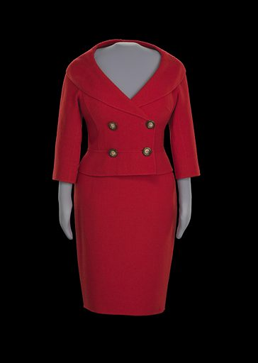 """This red suit, consisting of a jacket (.1) and skirt (.2), was designed by Céline and worn by Oprah Winfrey on an episode of The Oprah Winfrey Show that aired in September 2004. The suit is made from a red wool and nylon blend boucle fabric. The fitted jacket has a shawl collar with an open neckline and closes proper right side over left side at the center front with two (2) large round brown tortoise-shell plastic buttons with the text """"CELINE"""" etched on them and two (2) smaller buttons of the same design. The two (2) smaller buttons cannot be seen from the facing side. Two (2) additional decorative large round buttons of the same design are sewn on the proper right side corresponding to the placement of the functioning buttons on the proper left side. The 3/4–length sleeves are cut straight and do not have cuffs. The back of the jacket has seaming and pleating for a form-fitting silhouette, though the waistband around the front and back has a slight flare. The interior of the jacket is not lined. There are two (2) red transparent plastic buttons on the interior proper left front side that are backing the large tortoiseshell buttons on the facing side for stabilization. The large buttons on the proper right side are stabilized by the smaller tortoiseshell buttons. Three (3) labels are sewn at the interior center back neck. The top label is white fabric with gray embroidered text reading """"FINITION MAIN."""" The middle label is sewn to the bottom edge of the top label and is white fabric with gray embroidered text reading """"CELINE"""". The bottom label is sewn to the bottom edge of the middle label and is white paper with black preprinted text and handwritten black ink text with style, size, fiber content, and care information. Date: 2000s. Record ID: nmaahc_2016.7.3.1-2."""