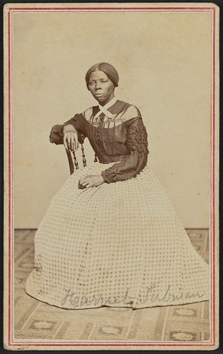 """A carte-de-visite of Harriet Tubman seated in an interior room. She is positioned slightly turned to the right and gazes off camera. Her right hand rests on the back of a wooden chair and her left hand rests in her lap. A body patterned carpet covers the floor and the wall or drop behind her is a blank light colour. Tubman wears a black bodice that buttons at the center front and has dropped sleeves with heavy ruching and ruffled details on the sleeves. There is a panel of lighter fabric around the yoke, with the upper neck the same dark colour as the body of the bodice. A white lace collar with short tails is crossed and pinned at the front of her neck. Her hair is parted at the center and gathered at the nape of her neck. Tubman's full skirt is made from a light and dark patterned gingham check. It drapes slightly on the floor and hides her feet completely. The text """"Harriet Tubman"""" is handwritten in graphite across the bottom of her skirt. The print is mounted on card stock and a double-lined red border is printed around the front edges of the card framing the print. Date: 1860s. Record ID: nmaahc_2017.30.47."""