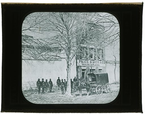 """Lantern slide of the slave trading firm of Price, Birch, & Co of Alexandria, Virginia. The slide depicts a three story building is set to the right of the slide. A sign on the building reads """"PRICE BIRCH & CO. / DEALERS IN SLAVES."""" A tree is at the center of the image. Arrayed in the foreground are a horse, covered wagon and 10 soldiers. The soldiers appear to be both white and African American, with a group of four black soldiers grouped together on the left and one standing alone back against the wall. All the men are in full uniform, including hats, rifles, and swords. Printed vertically on the left of the image is """"TH McALLISTER, Manufacturing Optician,."""" Printed vertically on the right side of the image is """"49 NASSAU STREET, NEW YORK."""" A paper label is adhered to the back of the slide. Handwritten vertically in ink is """"0290 Price, Birch & Co's Slave Pen / Alex. Va"""" The slide is in a metal frame. Date: 1860s. Record ID: nmaahc_2018.43.6."""