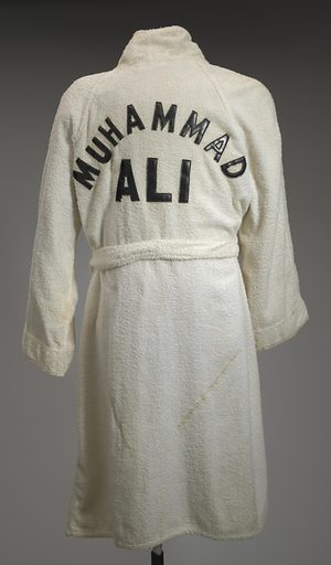 """This white cotton terry robe (a) and belt (b) were used by Muhammad Ali while training in 1980 at Deer Lake, Pennsylvania, for a fight against Larry Holmes. The robe has full-length sleeves, a turned collar, and falls just below the knees. There are two (2) patch pockets, one at each front side waist, with rounded bottom edges. A white rectangular patch with black text reading """"EVERLAST"""" is sewn to the proper left front chest. Two (2) self-fabric belt loops are sewn to the robe, one at each side waist, for securing the self-fabric belt (b). Black leather letters are sewn on the back across the shoulders reading """"MUHAMMAD / ALI"""" with the name Muhammad arcing over the name Ali. The robe is self-lined in white cotton terry. Date: 1980s. Record ID: nmaahc_2011.153.3ab."""