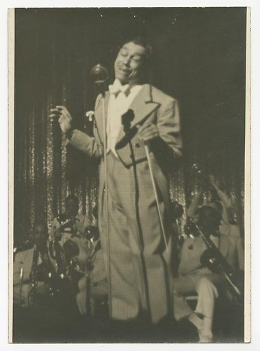 A black and white photograph of Cab Calloway wearing a checked tuxedo and singing into a microphone. Calloway is pictured in the center of the image, both arms bent at the elbow and raised chest high, a conductors baton held in his proper left hand and pointing downwards. His head is tilted slightly to his proper left, his eyes are closed and his mouth open and smiling slightly. The checked tuxedo has high-waisted pleated pants and a tail coat with dark coloured trim at the collar. He wears a white shirt and white bow tie. Behind him and slightly out of focus are seated band members. All wear light coloured suits and most hold their instruments in their hands, not playing. At the back right side, a trumpet player holds an upturned trumpet to play with both hands. Behind the band, a sequined curtain is partially visible where the spotlight on Calloway shines on it. There are no marks or inscriptions, front or back. Date: 1930s. Record ID: nmaahc_2013.237.11.