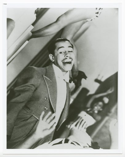 A black and white photograph of Cab Calloway performing with dancers around him. Calloway is pictured in the cente rof the image, pictured from the waist up at an angle from the bottom left corner. He wears a checked tuxedo with tail coat and white bowtie. His mouth his open as if singing and his is glancing down past his proper right shoulder. In the foreground, the hands, neck, chin, and torso of a dancer in a partial backbend is visible. Behind her, in the background, another dancer is visible, but out of focus. She wears a striped costume with white bodice and stands with one arm raised above her head, bending back slightly from the waist. Behind Calloway, only the legs of another dancer are visible. She is atop an elevated platform, behind and facing away from Calloway, standing upon her proper left foot with her proper right bent at the knee and her dark coloured high heeled shoe visible in the center of the image. There are no marks or inscriptions, front or back. Date: 1930s. Record ID: nmaahc_2013.237.16.