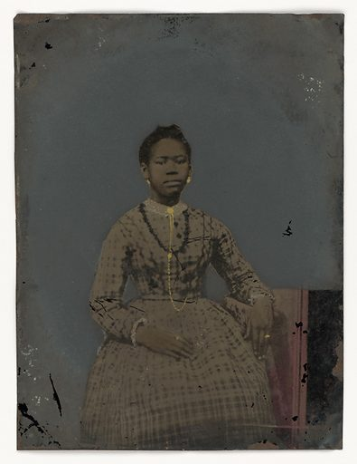A hand tinted tintype photograph of a young woman, seated. This portrait depicts a young woman sitting with her left arm draped over an armrest at her side. Wearing a plaid dress, her right hand resting in her lap, she gazes directly at eh viewer. Her image has been tinted by hand, highlighting her dress collar and cuffs with white detailing to resemble lace. Gold paint is used to give her a round gold brooch at her neck, with a long gold chain that fastens at her waist. She wears a gold ring on the forefinger of her right hand and on the ring finger of her left hand. Her hair is pulled back from her face and she wears gold tinted earrings. The background has been painted over and is a uniform dark grey. The arm rest at her left side is draped with a patterned cloth. There is an area of red staining in the bottom right corner. Date: 1850s. Record ID: nmaahc_2013.97.